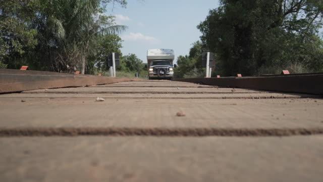 vídeos de stock, filmes e b-roll de pickup camper driving over a wooden bridge in the jungle - estrada rural