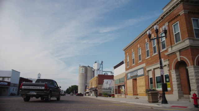 Pickup farm truck makes the corner on main street in front of a generic bank in small town USA.