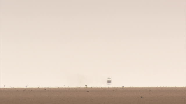 a pickup kicks up dust on a distant, flat horizon. available in hd. - 熱波点の映像素材/bロール