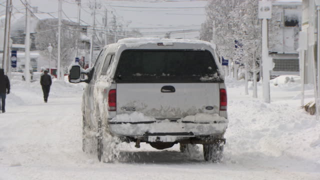 Pickup passing camera and several pedestrians on snowy city street after storm