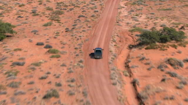 A pickup truck drives on desert road near  Lake Powell, Utah.