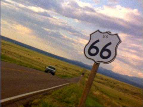 vidéos et rushes de canted pickup truck driving toward camera on road on plains / zoom in to route 66 road sign in foreground - route 66