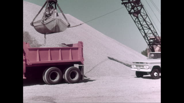 ws pan pick-up truck moving at construction site, crane loading sand in dump truck / united states - 1960 stock-videos und b-roll-filmmaterial