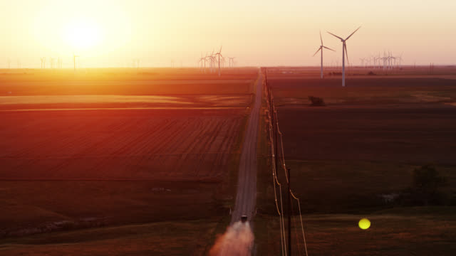 pick-up truck on country road between fields and wind turbines at spearville wind farm, kansas - 逆光点の映像素材/bロール