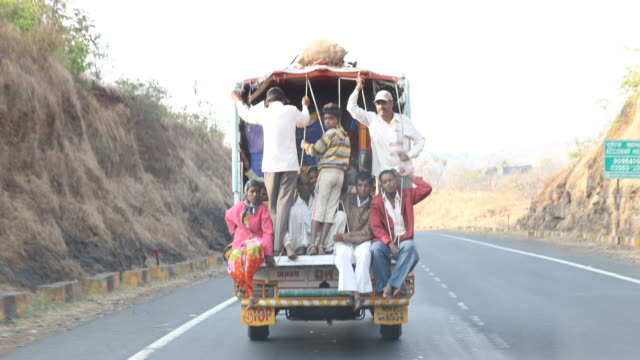 a pickup truck overloaded with standing and sitting passengers in the rear on the way to the city of mumbai india - pick up truck stock videos and b-roll footage