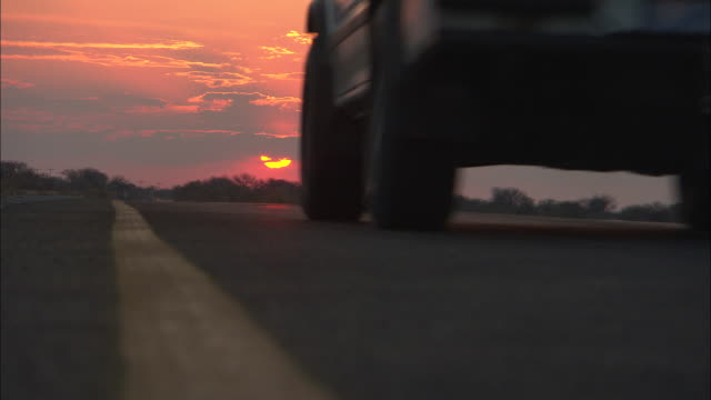 MS, LA, Pick-up truck  passing camera on desert road at sunset, view from ground, rear view, South Africa