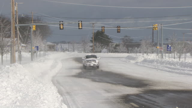 vídeos de stock e filmes b-roll de pickup truck passing camera on deserted snowy street with wind blowing snow - rhode island