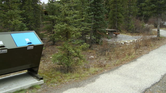 vídeos de stock e filmes b-roll de ws pan picnic table and bear proof garbage bin at footpath / lake louise, alberta, canada - mesa de piquenique