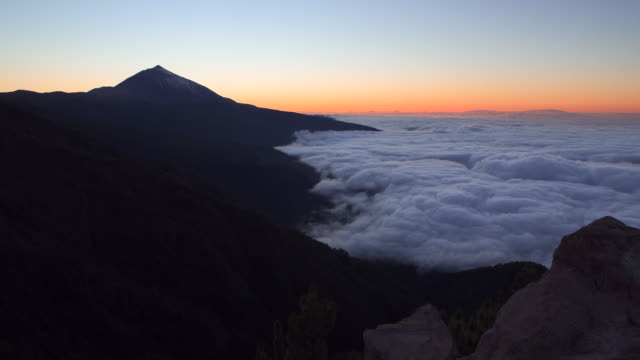 pico del teide volcano (the highest mountain of spain) at sunset with clouds down at the valley. - unesco stock videos & royalty-free footage