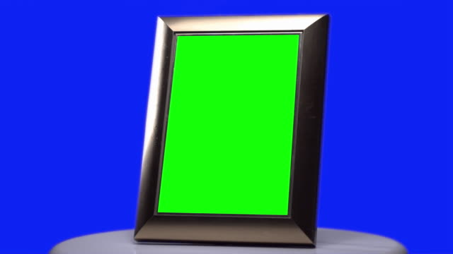 picture frame green screen slowly turning with blue screen background - photo album stock videos and b-roll footage