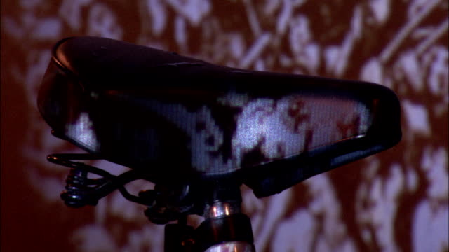 a picture is projected onto a bicycle seat and the wall behind it. available in hd. - bicycle seat stock videos & royalty-free footage