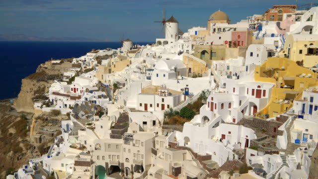 vídeos de stock, filmes e b-roll de picturesque cliffside town of oia on the mediterranean island of  santorini, greece - oia santorini