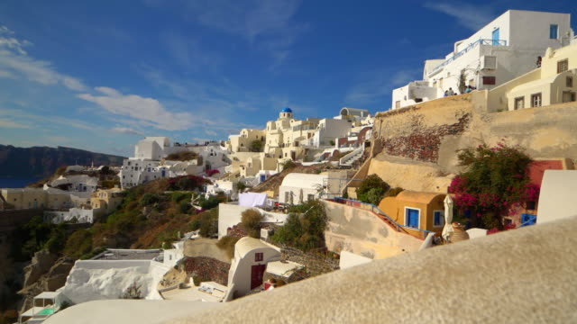 picturesque cliffside town of oia on the mediterranean island of  santorini, greece, slow motion - oia santorini stock videos & royalty-free footage