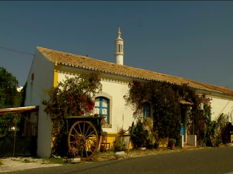 vídeos de stock, filmes e b-roll de picturesque cottage with flowers and cart outside ornate chimney on roof truck drives past algarve - trepadeira