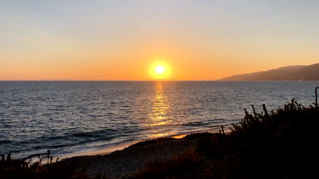 picturesque sunset at zuma beach in malibu. the western fires and smoky haze add a reddish hue to the sun. - malibu stock videos & royalty-free footage