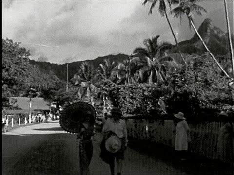 vídeos de stock, filmes e b-roll de picturesque view of black sand beach with waves and swaying palm trees pan across tropical harbor of avarua / main street man and woman with umbrella... - polinésia
