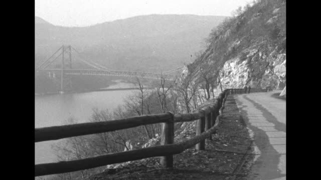 picturesque views of the completed bear mountain bridge / a slow pan down of a line of model t automobiles driving forward underneath the... - フォード・t型モデル点の映像素材/bロール