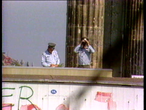 stockvideo's en b-roll-footage met of piece of barbed wire near berlin wall; east german guards on top of wall looking through binoculars; graffiti on wall in front of brandenburg... - berlijnse muur