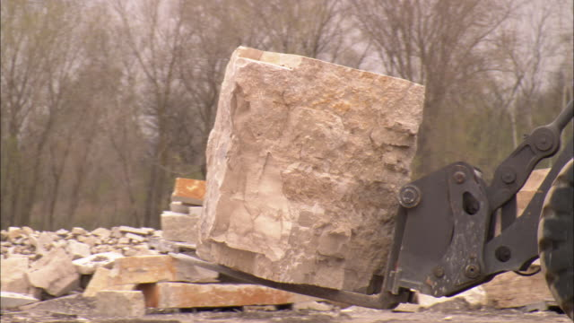 stockvideo's en b-roll-footage met a piece of heavy equipment carries a huge slab of limestone at a quarry. - steengroeve