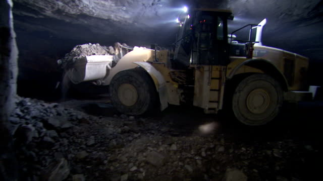 a piece of heavy machinery moves dirt in a tunnel. - sottosuolo video stock e b–roll