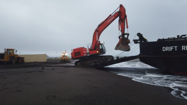 vídeos de stock e filmes b-roll de piece of machinery is driven onto a barge at the completion of a job to widen the beach area to protect the village airstrip from coastal erosion due... - erodido