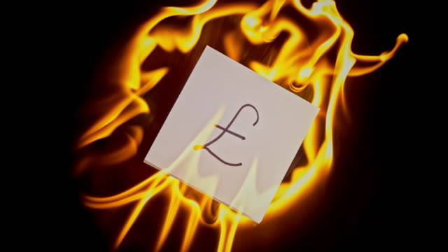 slo mo ld piece of paper with pound sterling sign on it catching fire - pound sterling symbol stock videos & royalty-free footage