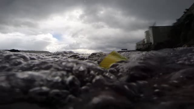 piece of plastic in sea being washed ashore low angle shot plymouth - sea stock videos & royalty-free footage