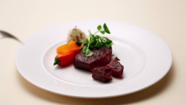 vídeos de stock, filmes e b-roll de cu piece of steak being picked up with forks / seoul, south korea - garfo