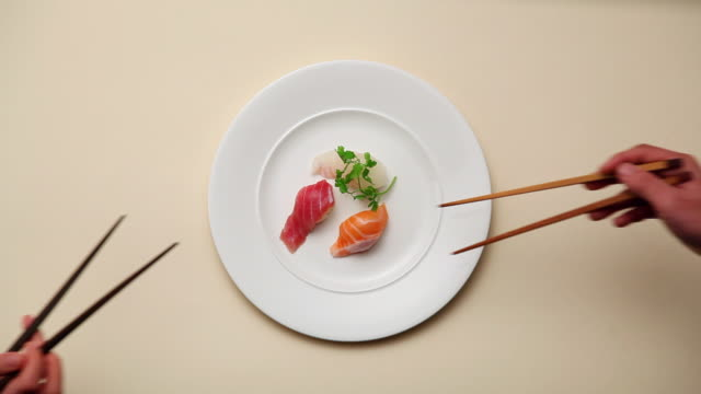 vidéos et rushes de cu piece of sushi being picked up with chopsticks / seoul, south korea - dessus