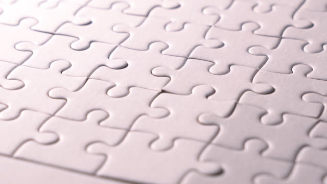 piece of white jigsaw filling by hand , concept: cooperation, teamwork, creativity, and access solution. - puzzle stock videos & royalty-free footage