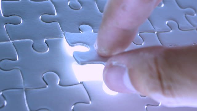 piece of white jigsaw puzzle filling by hand with lighting, success completing concept, 4k resolution. - part of stock videos & royalty-free footage