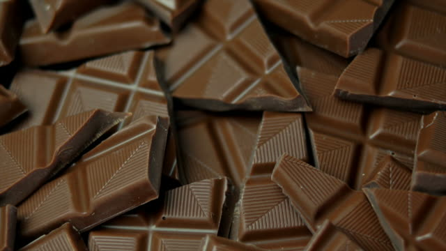 pieces of chocolate tracking shot (4:2:2 @ 100 mb/s) - chocolate stock videos & royalty-free footage