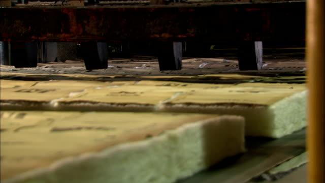 pieces of fiberglass insulation move along a conveyor belt after being cut by a machine. - fibreglass stock videos and b-roll footage