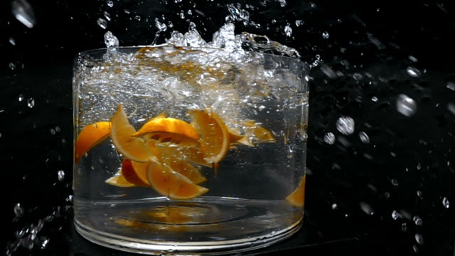 pieces of lemon fall into a large bowl of fresh water creating a splash as the camera revolves around it in slow motion. - david ewing stock videos & royalty-free footage