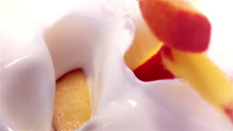 pieces of peach falling into yogurt in real slow motion