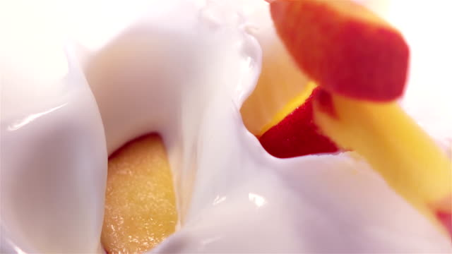 pieces of peach falling into yogurt in real slow motion - yoghurt stock videos and b-roll footage
