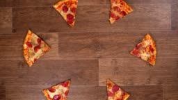 Pieces of pizza are separated and moved away in different directions and then collected, stop motion animation