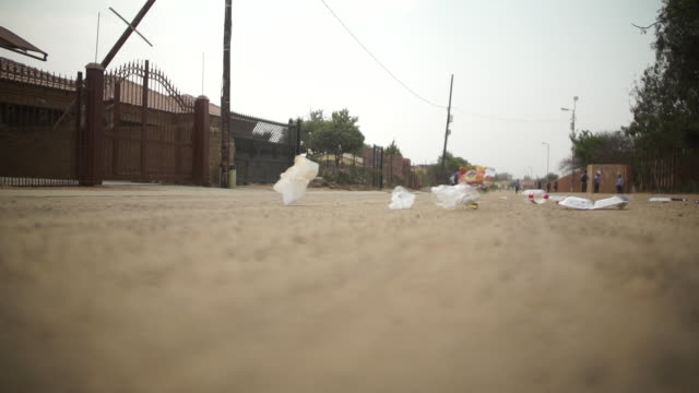 la slo mo pieces of trash rolling on the ground coming towards camera/ pretoria/ south africa - 巻く点の映像素材/bロール