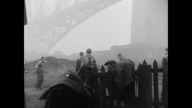 b/w pier and mist on the firth, cargo ship approaching dock, dockyard workers playing ball game, the forth bridge, and children playing beneath it / rosyth, scotland, united kingdom - 1940 stock videos & royalty-free footage