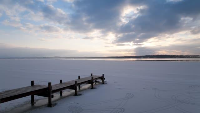 tl ws pier at frozen lake starnberg at winter sunset - ruhige szene stock-videos und b-roll-filmmaterial