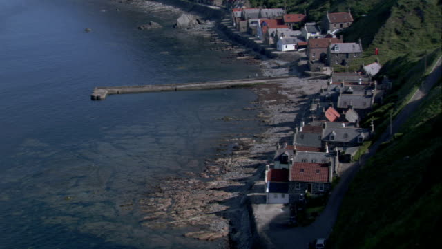a pier extends into the water near cottages in crovie, scotland. available in hd. - クロヴィー点の映像素材/bロール