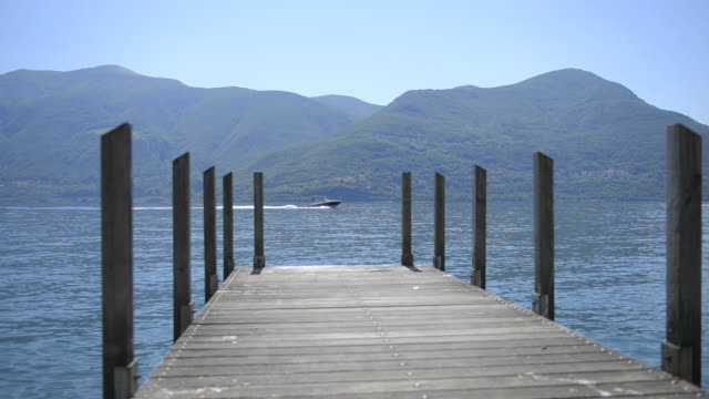 pier on a lake and a boat passing by. - named wilderness area stock videos & royalty-free footage