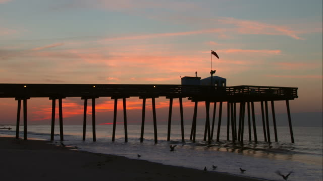 vídeos de stock, filmes e b-roll de pier on the beach in ocean city at sunrise - biruta