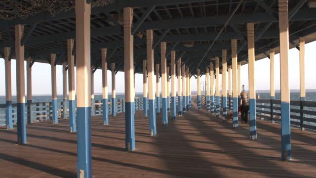 Pier Pillars Dog Walking Sunset Shadows