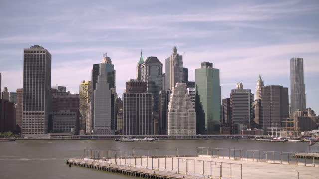 vidéos et rushes de a pier projects into the east river from brooklyn overlooking skyscrapers of manhattan, new york city, usa. - groupe moyen d'objets