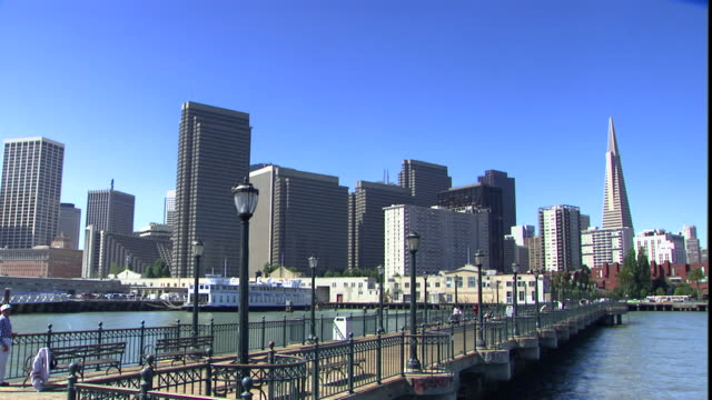 a pier stretches into the harbor past the san francisco skyline. - pier stock-videos und b-roll-filmmaterial