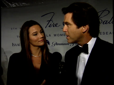 Pierce Brosnan and Kelly Shaye Smith talk to reporters on the red carpet