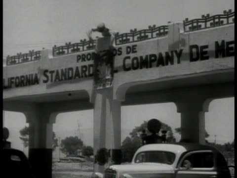 ws 'pierce' oil trucks leaving parking lot la ws mexican man hanging lazaro cardenas caricature poster on bridge overpass ms poster put on wall over... - 1935 stock videos and b-roll footage