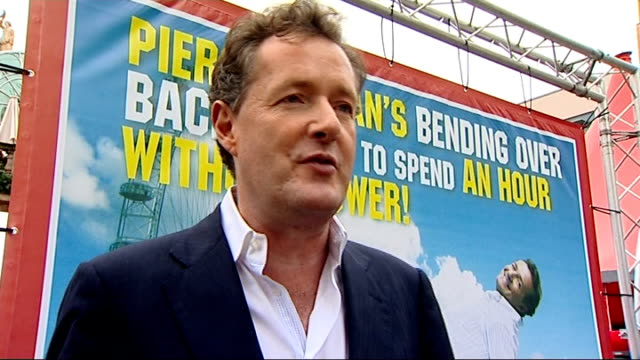 piers morgan launches spend an hour without power' campaign; ext large hoarding with slogan 'piers morgan's bending over backwards to spend an hour... - britain's got talent stock-videos und b-roll-filmmaterial