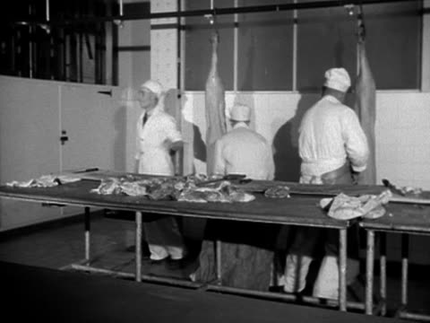 Pig carcasses are cut up in a sausage factory 1953